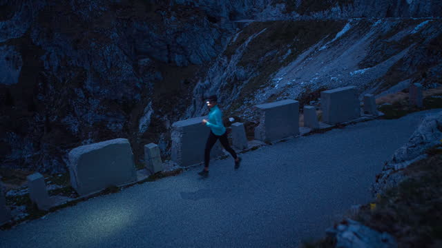 stockvideo's en b-roll-footage met health oriented woman jogging on a mountain pass road in the evening - jogster