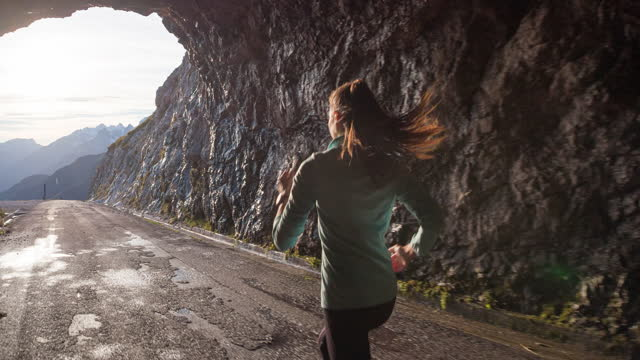 health oriented woman running through rocky tunnel high up in the mountains - motivation stock videos & royalty-free footage