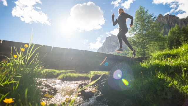 health oriented young athletic fitness woman running across wooden bridge over mountain spring in green landscape - ruscello video stock e b–roll