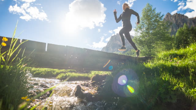 health oriented young athletic fitness woman running across wooden bridge over mountain spring in green landscape - sorgente video stock e b–roll
