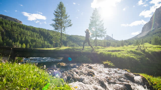 Gesundheitsorientiertes junge sportliche Fitness-frau läuft auf einem hölzernen Pfad in einer grünen Landschaft am Wasser
