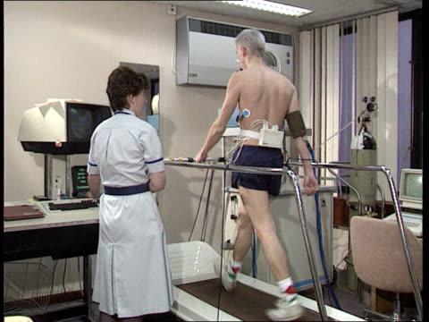stockvideo's en b-roll-footage met private health care: new rules; lib england: int people in reception area of private hospital bv man walking on treadmill feet on treadmill... - aan elkaar bevestigd