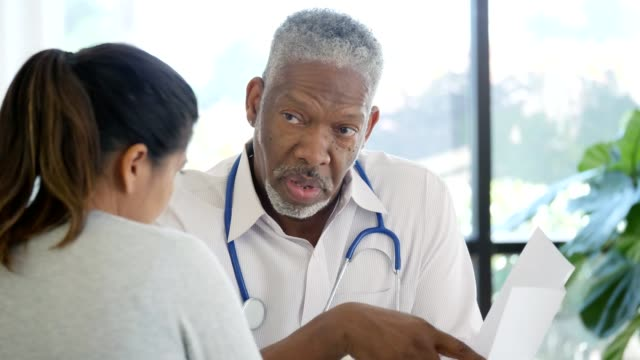 health professional explains to patient medical test results - rapporto video stock e b–roll