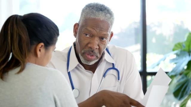 vídeos de stock e filmes b-roll de health professional explains to patient medical test results - resultado de exame