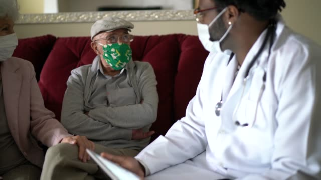 health visitor and a senior couple during home visit - visit stock videos & royalty-free footage