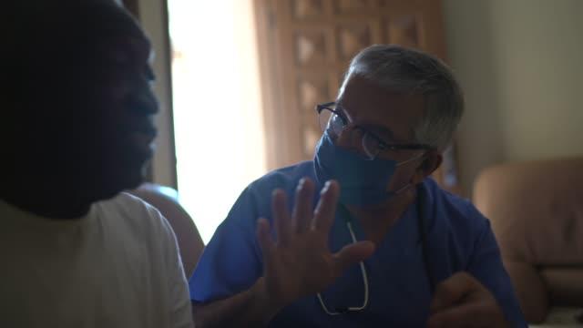 vídeos y material grabado en eventos de stock de visitante de salud y un hombre de la tercera edad durante la visita a casa - visita a domicilio