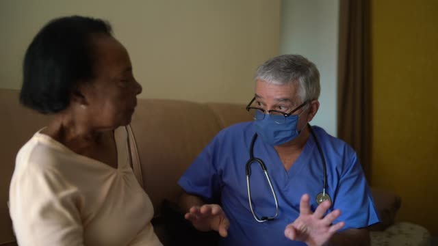 health visitor and a senior woman during home visit - non us film location stock videos & royalty-free footage