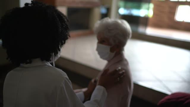 hälsa besökare och en äldre kvinna under hembesök - lyssna på hjärtslag bildbanksvideor och videomaterial från bakom kulisserna