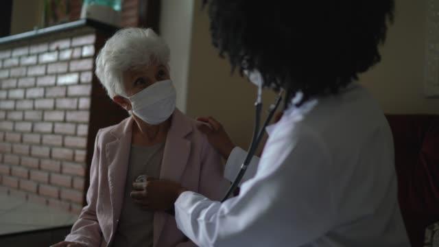 hälsa besökare och en äldre kvinna under hembesök - övervakningsutrustning bildbanksvideor och videomaterial från bakom kulisserna