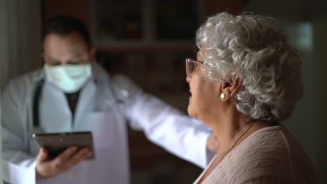 stockvideo's en b-roll-footage met de bezoeker van de gezondheid en een hogere vrouw tijdens huisbezoek - woongemeenschap ouderen