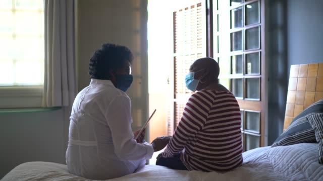 vidéos et rushes de visiteur de santé et une femme aînée pendant la visite de maison de soins infirmiers - back lit