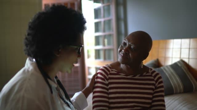 vídeos de stock e filmes b-roll de health visitor and a senior woman during nursing home visit - visit