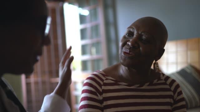vídeos de stock, filmes e b-roll de visitante de saúde e idosa durante visita a asilo - câncer tumor