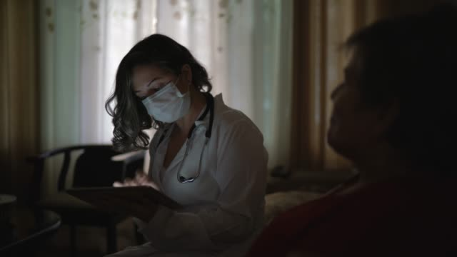 vídeos de stock e filmes b-roll de health visitor asking with digital tablet to a senior woman during home visit - enfermeira