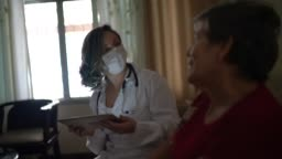 Health visitor asking with digital tablet to a senior woman during home visit