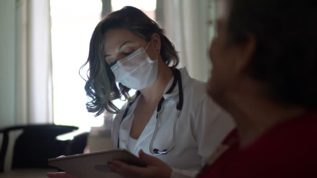 health visitor asking with digital tablet to a senior woman during home visit - visit stock videos & royalty-free footage