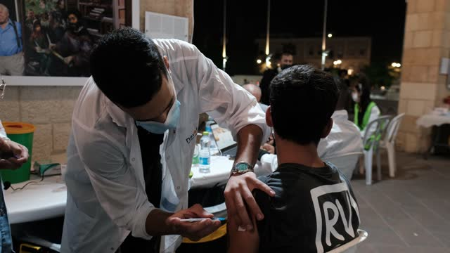 health worker administers a dose of the pfizer-biontech covid-19 vaccine to an israeli teenager at the open night vaccination center in the city hall... - teenage boys stock videos & royalty-free footage