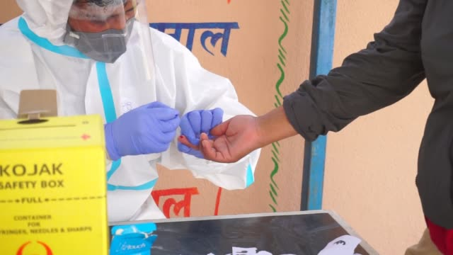 a health worker dressed in protective gear takes a blood sample from a man for a covid19 rapid test during a governmentimposed nationwide lockdown as... - kit di analisi video stock e b–roll