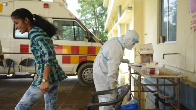 stockvideo's en b-roll-footage met health worker in personal protective equipment collects a nasal swab sample from locals for covid-19 rapid antigen testing , at a hospital in... - informatiebord