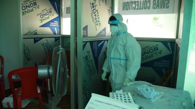 stockvideo's en b-roll-footage met august 2020 a health worker takes a fan in a hot summer day at a swab collection centre for covid19 coronavirus in guwahati on tuesday 18 august 2020 - testkit