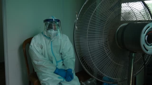 stockvideo's en b-roll-footage met august 2020 a health worker takes a fan to beat the heat wearing ppe kit in a swab collection centre for covid19 coronavirus test in guwahati on 30... - testkit