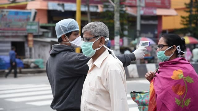 health worker thermal screening a man before boarding a bus - india stock videos & royalty-free footage