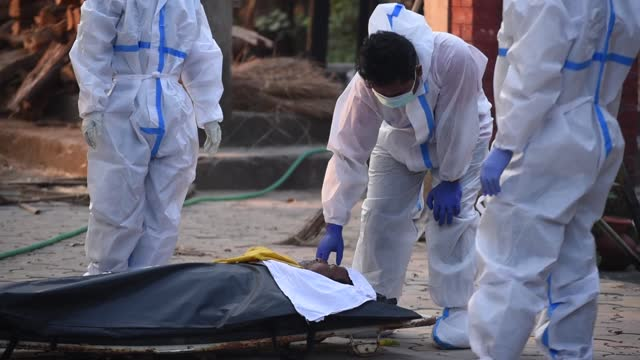 health worker wearing ppe kit unzips a dead body cover to show the face to family members, who died of covid-19 coronavirus, at a cremation place, in... - the human body stock videos & royalty-free footage