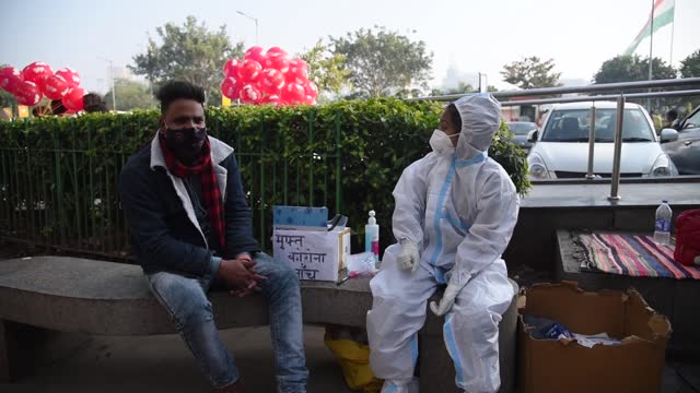 health worker wearing ppe kit waiting for people to collection swab sample for coronavirus test, at connaught place in new delhi on 12 january 2021.... - asian stock videos & royalty-free footage