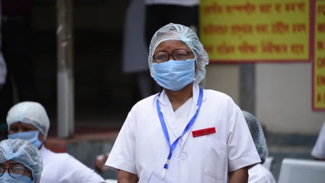 health worker wearing protective mask and head cap - india stock videos & royalty-free footage