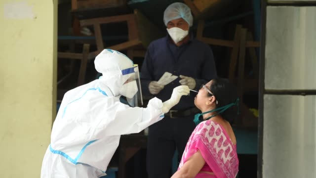 stockvideo's en b-roll-footage met a health worker wearing protective wear collecting swab sample for covid19 test at a coronavirus screening centre in guwahati india on saturday 11... - testkit