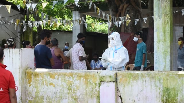 stockvideo's en b-roll-footage met health worker wearing protective wear collecting swab to rapid test for covid19 at a covid19 hotspot zone in pandu area of guwahati india wednesday... - testkit