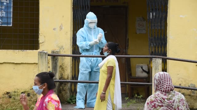 stockvideo's en b-roll-footage met health worker wearing protective wear collecting swab to rapid test for covid19 at a screening centre in guwahati india 18 july 2020 guwahati has... - testkit
