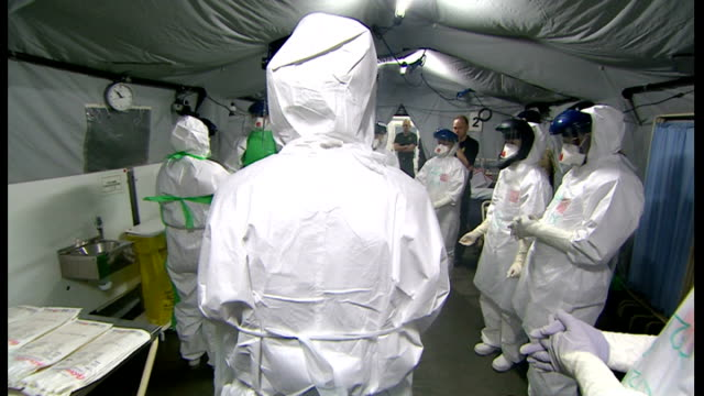 health workers ebola training with army medical services training are with people wearing protective suits outside tent / health workers undergoing... - laptop bag stock videos and b-roll footage