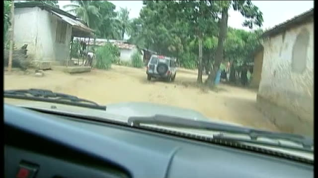 Health workers strike over hazard payment SIERRA LEONE Freetown EXT POINT OF VIEW forward from car along dirt track in village of Lumpur Village...