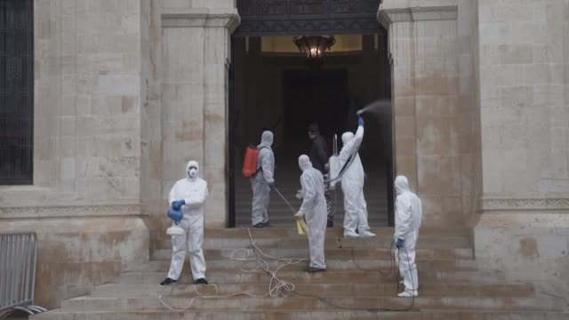 health workers wearing hazmat suits spray the lebanese parliament in downtown beirut with disinfectant as fears rise over the spread of coronavirus... - spray stock videos & royalty-free footage
