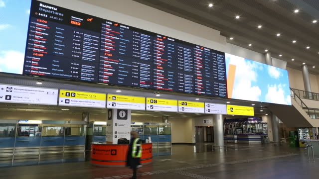 health workers wearing protective suits and face masks prepare for screenings at the passenger arrivals area as the number of coronovirus cases... - annusare video stock e b–roll