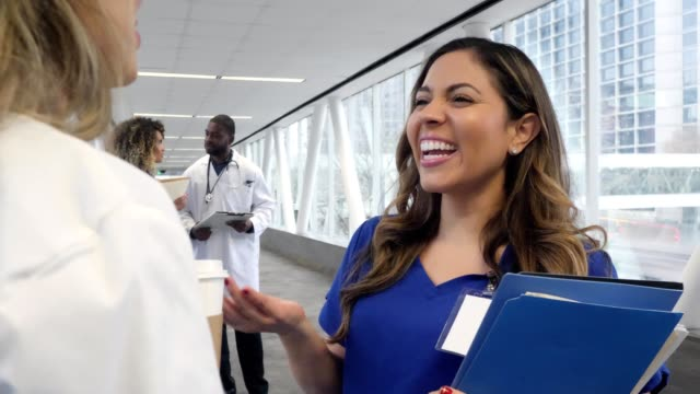 healthcare colleagues talk in hospital corridor - scrubs stock videos & royalty-free footage