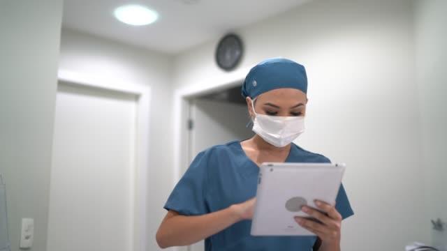 healthcare female worker walking using digital tablet at hospital - nurse walking stock videos & royalty-free footage