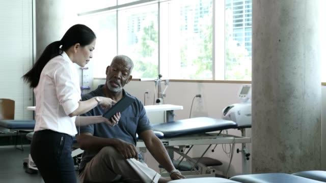 vídeos de stock, filmes e b-roll de profissional de saúde pergunta ao paciente sênior sobre seu histor médico - fisioterapeuta