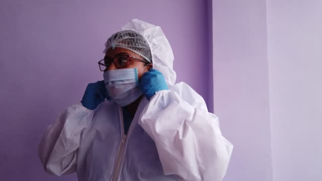 healthcare professional getting ready for the new normal day at work facing the global crisis by wearing a full body protective suit - full suit stock videos & royalty-free footage