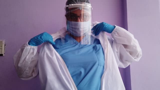 stockvideo's en b-roll-footage met healthcare professional getting ready for the new normal day at work facing the global crisis by wearing a full body protective suit - compleet pak