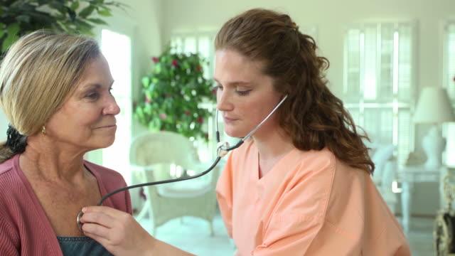 healthcare professional listening to heart of woman - hembesök bildbanksvideor och videomaterial från bakom kulisserna
