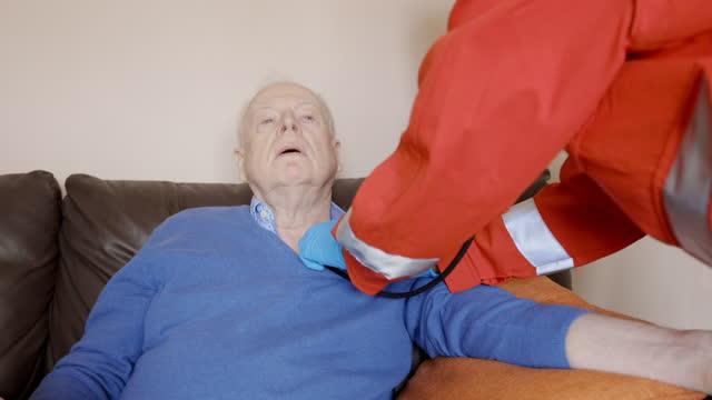 operatore sanitario in casa che controlla il paziente anziano durante la pandemia - apparato respiratorio video stock e b–roll