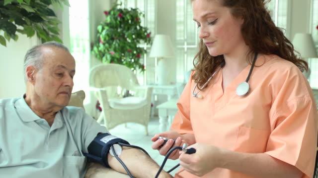 vídeos de stock, filmes e b-roll de profissional de saúde a pressão sanguínea de male - visita