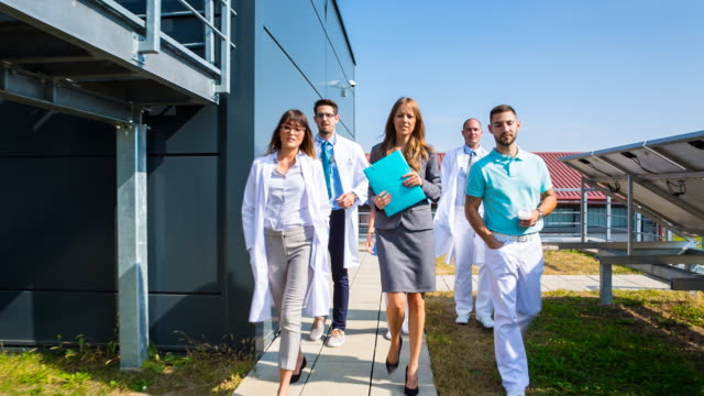 vídeos de stock e filmes b-roll de ms healthcare professionals walking in front of clinic - aproximar imagem