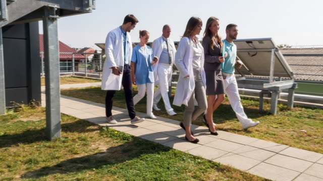 MS healthcare professionals walking in front of clinic