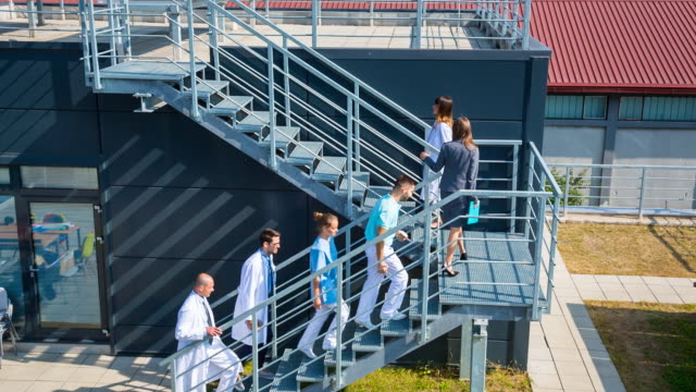 ha healthcare professionals walking on staircase in front of clinic - staircase stock-videos und b-roll-filmmaterial