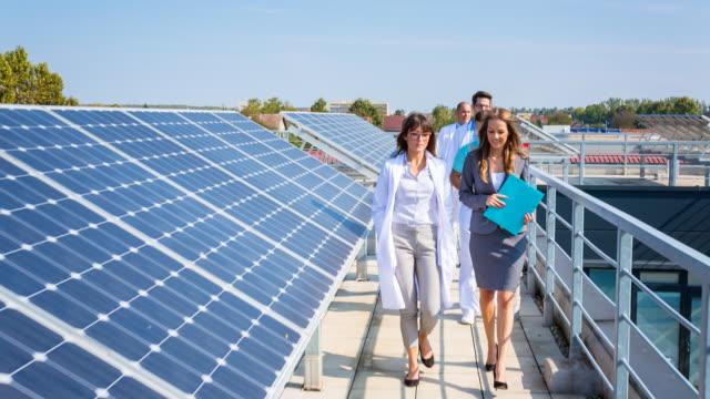 HA healthcare professionals walking past solar panel