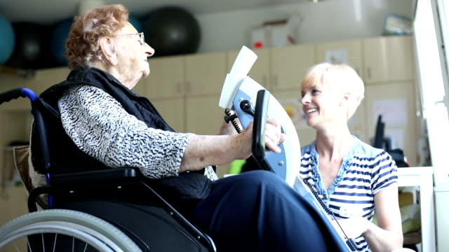 Healthcare Worker Assisting Senior Woman in Physiotherapy Exercise