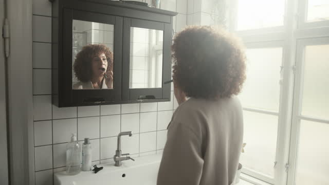 healthcare worker brushing teeth in bathroom - bathrobe stock videos & royalty-free footage